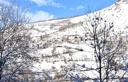 Winter landscape with small mountain village on a snowy slope with trees. Lugo, Spain. royalty free stock image