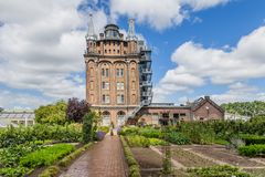 Ancent water tower in Dordrecht, Netherlands. Ancient water tower, rebuild and converted into an hotel and restaurant with a vegetable garden called Villa royalty free stock images