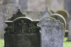 Ancestry. Ghostly graveyard headstones. Hazy selective focus image of an ancient English cemetery Stock Image