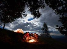 Anche campeggio nelle montagne Gli amici stanno sedendo intorno al fuoco con la birra che godono della festa immagini stock libere da diritti