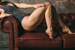 Anche e natiche resilienti delle gambe di misura bella ragazza sportiva nell'ente lussuoso del costume da bagno che posa sopra co fotografie stock