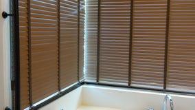 Anche la luce del sole fuori dei ciechi, del sole e dell'ombra di legno di finestra sui ciechi di finestra, interno decorativo ne immagine stock