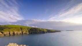 Anche luce sulle scogliere di Ceredigion e l'isola del cardigan da Mwnt, Galles immagini stock libere da diritti