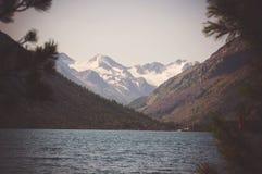 Anche paesaggio con il lago calmo su un fondo delle montagne scure Fotografia Stock