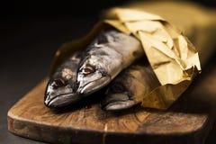 Anchois de poissons de maquereau sur la planche à découper et le plat en bois photos libres de droits