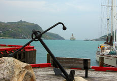 The Anchor. Large anchor on a dock, with a yacht and ocean liner leaving harbor Stock Photo