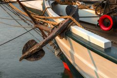 Anchor against Side of 101 Year Old Sailboat. Historic wooden schooner stock photo