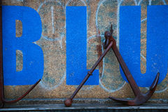 Anchor and blue character wall. Concrete wall of rusted anchor and blue character Royalty Free Stock Photos