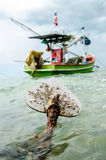 Anchor. Boat anchor and fishingboat floating in the sea Stock Photos