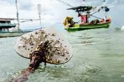 Anchor. Boat anchor and fishingboat floating in the sea Stock Photography