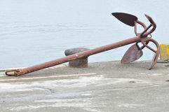Anchor and bollard. Anchor on the shore has been idle for some time Royalty Free Stock Images