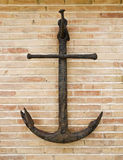 Anchor on a brick wall. Iron anchor hanging on a brick wall Stock Photos