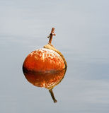 Anchor Buoy. A rusty anchor buoy and rope reflected in still morning waters Stock Photo