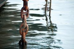 Anchor Chain. Rusty anchor chain hanging in the water Stock Photos