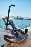 Anchor on embankment and cruiser in port Stock Photos