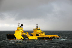 Anchor handling of Semi submergible in North Sea. Two yellow and black Anchor handling vessels engaged in towing a Semi Submergible Rig Royalty Free Stock Photography