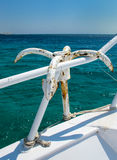 Anchor Hanging on the Handrail of a Yacht. Calm water of the Red Sea. Anchor hanging on the handrail of a yacht. Horizon over water. Blue summer sky Royalty Free Stock Image
