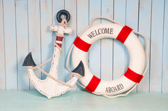 Anchor and life buoy on a background of white shabby wall boards Stock Images
