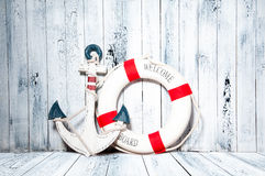 Anchor and life buoy on a background of white wall. stock photos