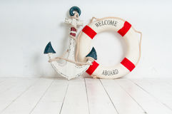 Anchor and life buoy on a white wooden floor Stock Photos