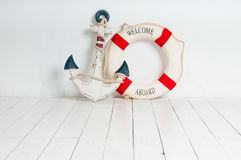 Anchor and life buoy on a white wooden floor Royalty Free Stock Image