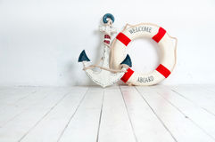 Anchor and life buoy on a white wooden floor Stock Photography