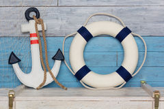 Anchor and life buoy on wood background blue-white Stock Photography