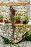 Anchor near the wall with flowers. Anchor near the wall with red flowers in pot Stock Photo