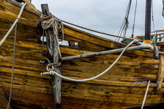 Anchor on an old 1400's replica ship. Planks, ropes, pulleys, tackle, anchor, and rigging of an old replica of a 1400's era sailing ship stock images