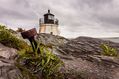 An anchor stands out in the dramatic rocky coastline at Castle Hill Lighthouse in Newport, Rhode Island, under a stormy sky royalty free stock photo