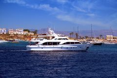 Private motor yacht approaching to anchorage in Tabarca island. Anchorage zone in the island of Tabarca in the East coast of Spain and all type of yachts Royalty Free Stock Photos