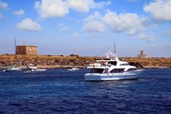 Private motor yacht approaching to anchorage in Tabarca island. Anchorage zone in the island of Tabarca in the East coast of Spain and all type of yachts Stock Image
