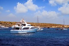 Private motor yacht approaching to anchorage in Tabarca island. Anchorage zone in the island of Tabarca in the East coast of Spain and all type of yachts Stock Photos