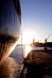 Cargo Ship Anchored - Sunset Scenery - Economy. A cargo ship anchored on a wharf at sundown. Silhouette of cranes on the horizon Stock Photo