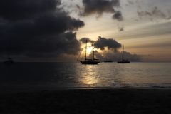 Sunset beach sailing boat stock photography