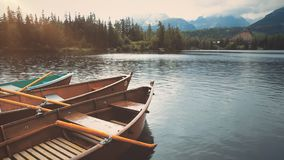 Anchored boat on mountain summer lake close up. House in Pine Woods. Rural View of Mountainous Forest on Background. Slovakia Tourism. Floating Kayak on Smooth stock video