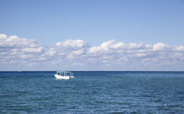 Anchored boat on ocean on sunny day a Stock Photo