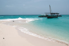 Anchored boat by the sandy beach. A relaxing scenery of sandy beach and Indian Ocean with some boats at the shore of an island which disappears with high tide Stock Images