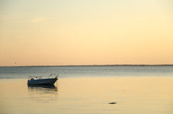 Anchored boat in sunset colors Royalty Free Stock Photos