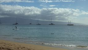Shoreline of a Maui, Hawaii Beach During Summer. Anchored boats ride gentle waves while people enjoy the waters off a Maui, Hawaii beach in the late afternoon stock video