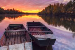 Anchored boats on the river with dramatic, gorgeous sunrise. Gorgeous colorful sunrise with dramatic cloudscape over Tisza river in Hungary with anchored boats stock images