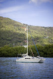 Anchored catamaran. Luxury catamaran anchored just off sure a lush green mountain in the tropics Stock Images