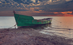 Anchored fishing boat on sandy beach of the Baltic Sea Stock Image