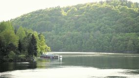 Anchored motorboat at pier on lake. Boat is parked at dam stock footage