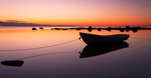 Anchored rowing boat at sunset. A rowing boat anchored with two ropes at sunsets. Due to calm weather, the water is flat and creates reflections Royalty Free Stock Photo