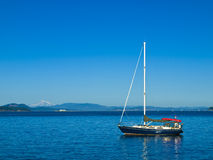Anchored sailboat. Sailboat anchored near the shore with mountain range as a backdrop Stock Images