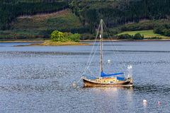 Anchored sailboat at Glencoe. GLENCOE, HIGHLAND, SCOTLAND - SEPTEMBER 24, 2014: lone wooden vintage sailboat moored at Loch Leven with an island in background in Royalty Free Stock Photos