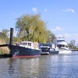 Anchored sailing ship and motorboats Stock Photos