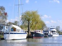 Anchored sailing ship and motorboats Stock Photo