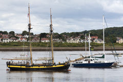 Anchored ships on a quiet sea. A vessel and two smaller ships anchored near Conwy, Wales Stock Photos